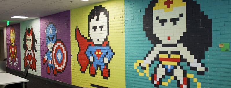 Un open-space décoré de post-it représentant des super-héros